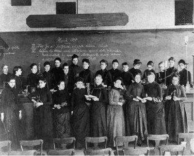 An 1888 photograph showing the twenty-four female students of MIT (and Ellen Swallow Richards, an early graduate of the institute and then its first female instructor). Sophia Hayden is at the far left of the front row, holding a T-Square as a symbol of her field of study. MIT Museum