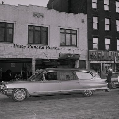 Beverly Greene, Unity Funeral Home, Harlem, New York City, 1953. This photograph, taken February 22, 1965, shows the hearse bearing Malcolm X's body pulling up in front of the Unity Funeral home, where thousands of people paid their final respects to the slain black activist. Getty Images, Bettman collection